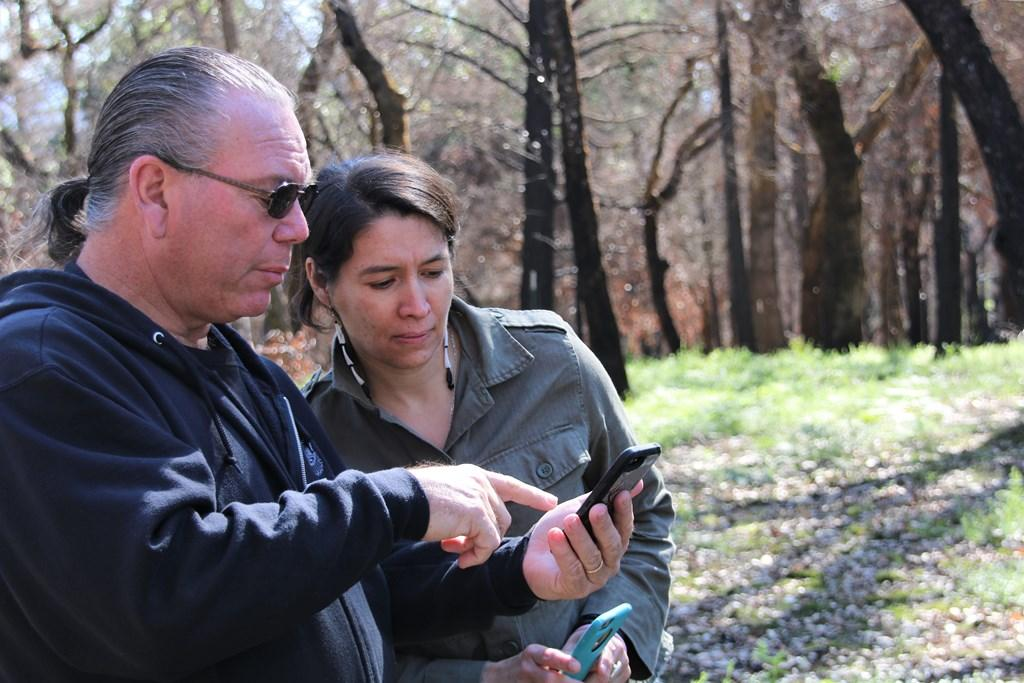 Clint McKay shows Allison Herrera some shots of the burn zone immediately after the fire sm